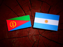 Eritrean flag with Argentinian flag on a tree stump. Eritrean flag with Argentinian flag on a tree stump Stock Photography