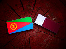 Eritrean flag with Qatari flag on a tree stump isolated. Eritrean flag with Qatari flag on a tree stump Royalty Free Stock Image