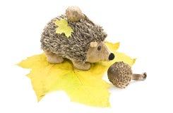Erizo del juguete en las hojas de arce. Fotografía de archivo