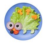Erizo graciosamente hecho de verduras en la placa azul Foto de archivo libre de regalías