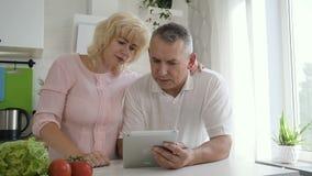 Erklärender älterer Ehemann der reifen Frau, wie man Tablet-Computer benutzt stock video footage