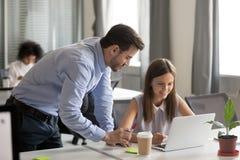 Erklärender junger weiblicher Angestellter der Aufgabe des freundlichen Mentors lizenzfreie stockbilder