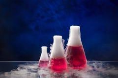 Erlenmeyer flaska med röd flytande på tabellen arkivbild