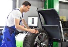 Ermüden Sie Änderung in einer Garage - den Versammlungsteilnehmer, der einen Reifen auf dem Mach balanciert stockfotografie