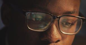 Ermüdet vom Arbeiten an dem jungen schwarzen Mann des Computers drückt seine Gläser hoch und reibt seine Augen Workaholic, schwer stock video footage