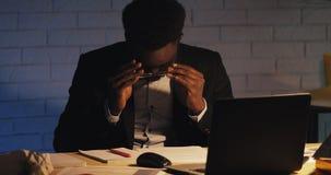 Ermüdet vom Arbeiten mit jungem schwarzem Mann der Dokumente drückt seine Gläser hoch und reibt seine Augen Workaholic, schwer ar stock video footage