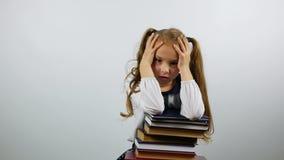 Ermüdet vom Lernen eines Schulmädchens auf dem weißen Hintergrund Das Mädchen, das einen Stapel von Büchern hält und schaut ersch stock video