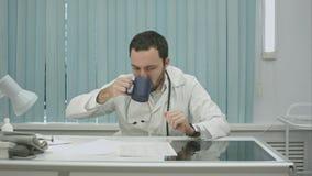 Ermüdet von der Arbeit, fahren bärtiges Doktorgetränk von der Schale fort und, mit Dokumenten und Röntgenstrahlen woking Stockbild