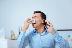 Ermüdeter Mann, der geht zu niesen Stockfotos