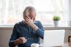 Ermüdeter reifer Mann, der die Gläser leiden unter müden Augen entfernt lizenzfreies stockbild