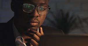 Erm?det vom Arbeiten an dem jungen schwarzen Mann des Computers dr?ckt seine Gl?ser hoch und reibt seine Augen Workaholic, schwer stock video