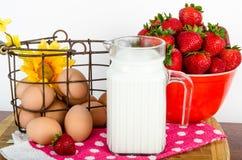 Ernährungsfrühstück von braunen Eiern, von Erdbeeren und von Milch Stockbild