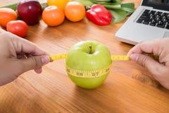 Ernährungswissenschaftler, der einen Apfel misst stockfotos