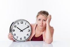 Ernüchterte schöne junge blonde Frau, die eine Uhr hält Stockbild