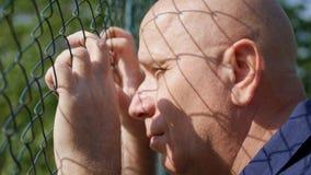 Ernüchtertes Mann-Bild, das durch einen metallischen Zaun traurig schaut lizenzfreie stockfotos