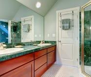 Erneuerndes hellgrünes Badezimmer mit hellen braunen Kabinetten Stockfotos