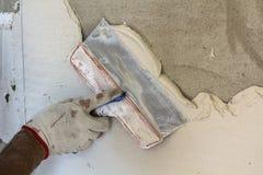 Erneuerungsarbeitskrafthand, welche die Wand vergipst stockbilder