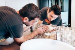 Erneuerungsdetails Baudetails mit dem Heimwerker oder Arbeitskraft, die Mosaikkeramikfliesen auf Badezimmerwänden hinzufügen stockbild