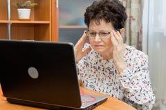 Ernste ältere Frau, die Brillen hält und zu Hause mit dem Notizbuch arbeitet Stockbild