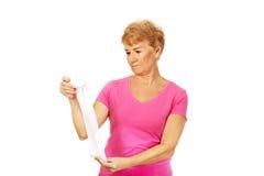 Ernste ältere Frau, die Verband hält Stockfotos