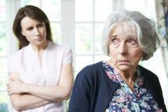 Ernste ältere Frau mit erwachsener Tochter zu Hause lizenzfreie stockfotografie