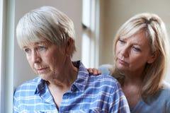 Ernste ältere Frau mit erwachsener Tochter zu Hause Stockfoto