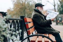 Ernste ältere männliche Person, die Pressebericht tut stockbilder