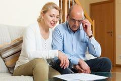 Ernste ältere Paare mit Finanzdokumenten stockfoto