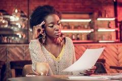 Ernste afroe-amerikanisch Frau, die beteiligt Papiere in den Händen betrachtet lizenzfreie stockfotografie