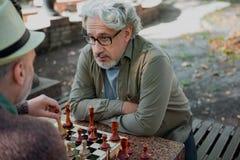 Ernste alte Männer, die im Vertrauen Schach spielen Stockfotos