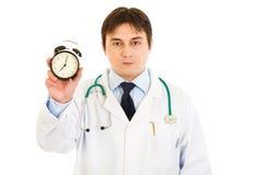 Ernste Arztholdingalarmuhr in der Hand Lizenzfreie Stockbilder