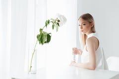 Ernste blonde Dame, die zuhause nahe Blumen sitzt Stockfotos