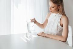 Ernste blonde Dame, die zuhause nahe Wasserkrug sitzt Stockbilder