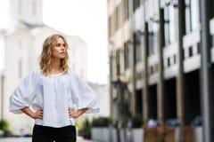 Ernste blonde Frau, die draußen steht und durchdacht Abstand untersucht Lizenzfreie Stockfotos