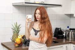 Ernste blonde Frau, die ein Glas an der Küche hält Stockfotografie