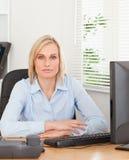 Ernste blonde Frau, die hinter einem Schreibtisch sitzt Stockfoto