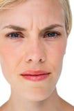 Ernste blonde Frau, die Kamera betrachtet Lizenzfreie Stockbilder