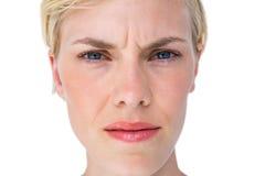 Ernste blonde Frau, die Kamera betrachtet Lizenzfreies Stockbild