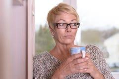 Ernste blonde Frau mit den Gläsern, die eine Schale halten Stockfoto