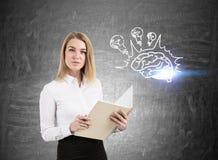 Ernste blonde Frau mit einem Buch und einer Gehirnbirne Lizenzfreie Stockbilder