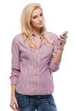 Ernste blonde Frau mit Mobiltelefon Lizenzfreies Stockfoto