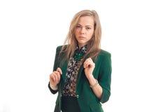 Ernste blonde Geschäftsfrau in der grünen Uniform, welche die Kamera betrachtet Stockfoto