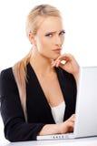 Ernste blonde Geschäftsfrau, die an Computer arbeitet Lizenzfreie Stockfotos