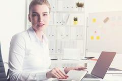 Ernste blonde Geschäftsfrau im Büro Stockfotografie