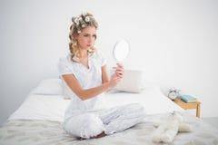 Ernste blonde schauende Reflexion auf angenehmem Bett Stockfotografie