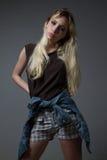 Ernste blonde Stellung und Betrachten der Kamera Lizenzfreies Stockfoto
