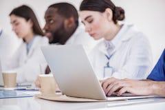 Ernste Doktoren, die Zusammenfassung auf Laptop in der Wohnung des Krankenhauses schreiben Lizenzfreie Stockfotografie