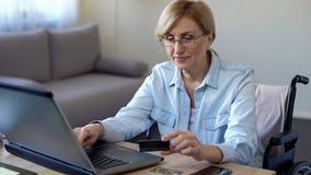 Ernste erwachsene Dame in hereinkommender Kartennummer des Rollstuhls auf dem Laptop, online kaufend stockfoto