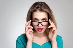 Ernste Frau in den Gläsern und mit den roten Lippen Lizenzfreie Stockfotos