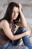 ernste Frau in den Jeans, die Loch haben, auf s zu sitzen Stockfoto